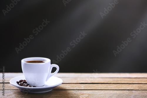 Wall Murals Cafe Cup of coffee and coffee grains on wooden table, on gray background