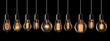 Leinwandbild Motiv Set of vintage glowing light bulbs on black background