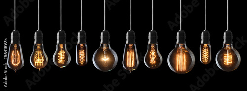 Obraz Set of vintage glowing light bulbs on black background - fototapety do salonu