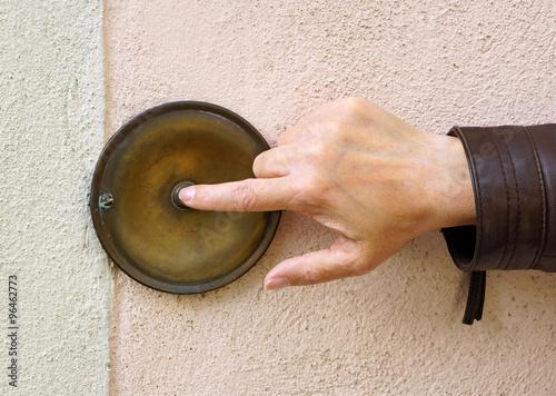 Fotografie, Obraz  Hand mit Klingel an Hauswand