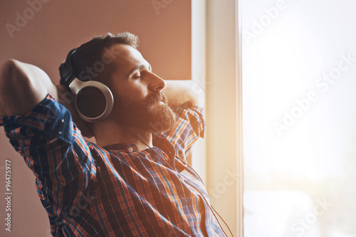 Photo  handsome bearded man  in headphones listening to music