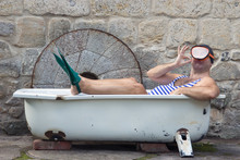 Man With Snorkeling Gear Lying In The Bathtub Outside