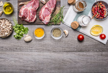 Two Steaks With Oil And Spices On Cutting Board  With Lemon, Salt And Meat Fork, Sliced Mushrooms, Napkin Border ,with Text Area On Wooden Rustic Background Top View