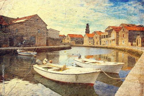 City on the water small bay for motor boats (town Hvar, Croatia). Picture in artistic retro style.
