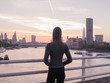 Young woman wearing hoodie on bridge in London at sunrise