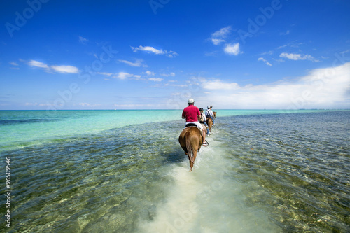 Fotografia, Obraz  People riding on horse back at the Caribbean beach. Grand Cayman