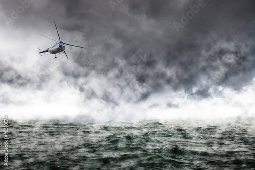 Tuinposter Helicopter A helicopter rescue mission in difficult stormy weather at sea.