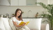 Pretty young woman relaxing on sofa with book and smiling at camera