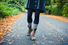 Legs Of Young Woman Walking In Autumn