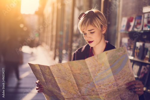 obraz lub plakat Young beautiful female traveler standing on the street and looking at the map