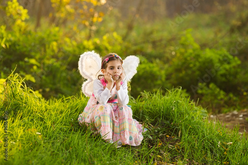 Poster Feeën en elfen Portrait of a cute little girl dressed up as a fairy sitting in a magical forest