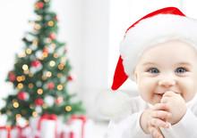 Happy Baby In Santa Hat Over Christmas Tree Lights