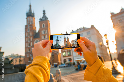 Fototapeta Female hands photographing with mobile phone old city center in Krakow obraz