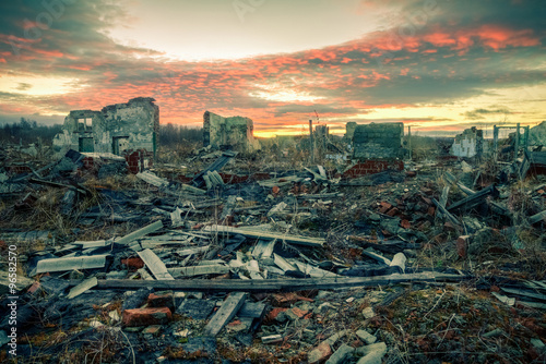 Photo  Apocalyptic landscape.The remains of destroyed houses at sunset