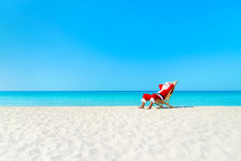 Christmas Santa Claus Resting On Sunlounger At Ocean Sandy Tropical Beach