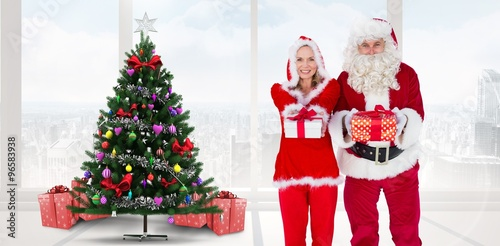Composite Image Of Santa And Mrs Claus Offering Gifts
