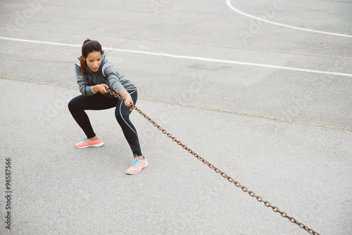 Fotografia  Fitness woman pulling chain for strength workout