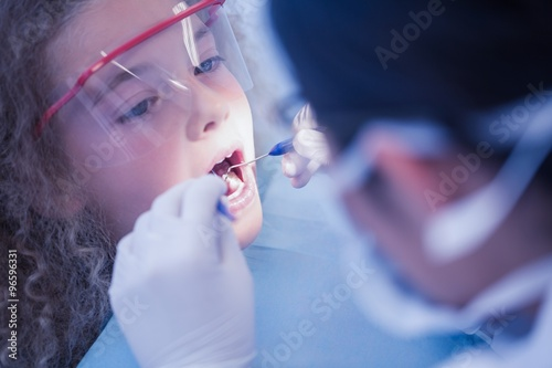 Little girl being examined by a dentist Poster