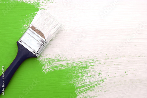 Paintbrush with white paint painting over green
