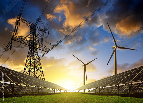 Fotografia  Solar panels with wind turbines and electricity pylon at sunset