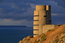 WW2 German Bunker, Jersey, U.K.  Telephoto Image Of An Uninhabited Ruin Of A Radio Tower From WW2, Lit By An Autumnal Sunset With Moody Skies And The Isle Of Sark In The Distance.