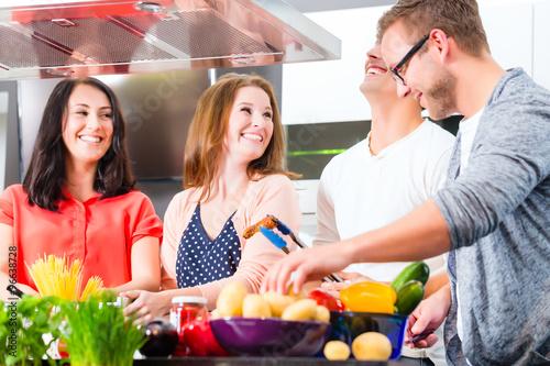 Obraz na plátně  Freunde kochen Spagetti und Fleisch zuhause in Küche