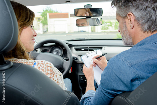 Fotografiet  Driving instructor and learner in front of car