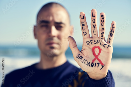 Fotografie, Obraz young man with a red ribbon for the fight against AIDS in his ha