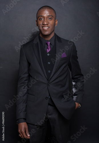 552a9a05f4e Studio fashion portrait of a handsome young African American businessman  wearing a black suit and tie