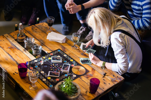 Fotografie, Tablou  Group of young people gathered to play Alias game