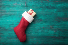 Red Santa Sock With Gift Box Over Wooden Background