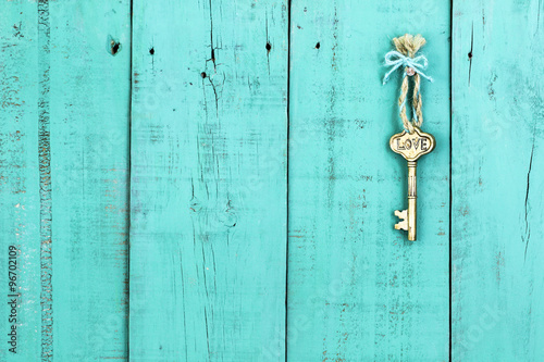 Fotografie, Obraz  Brass skeleton key with Love hanging by rope on antique rustic teal blue wood do