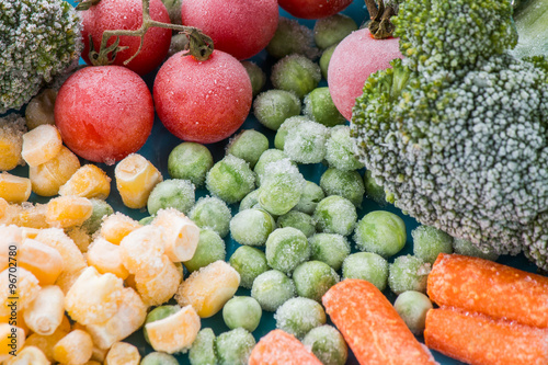 frozen vegetables: broccoli, cherry tomatoes, corn, pea, carrot on blue plate