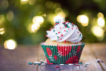 Christmas Cupcake With Red And Green Sprinkles On Rustic Table. Shallow Depth Of Field. Sparkling Christmas Tree Lights Background.