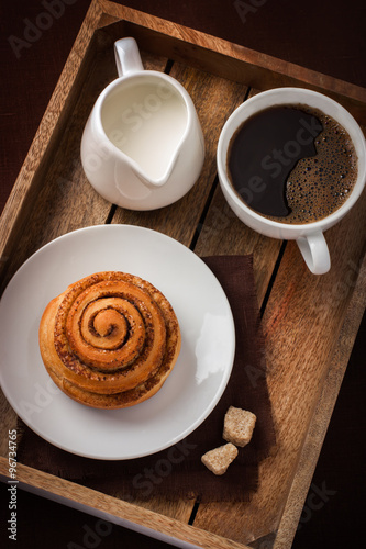Photo cinnamon roll,  cup of coffee and cream  on wooden tray