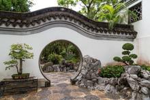 Bonsai Trees And Chinese Style Round Doorway At The Kowloon Walled City Park In Hong Kong, China.