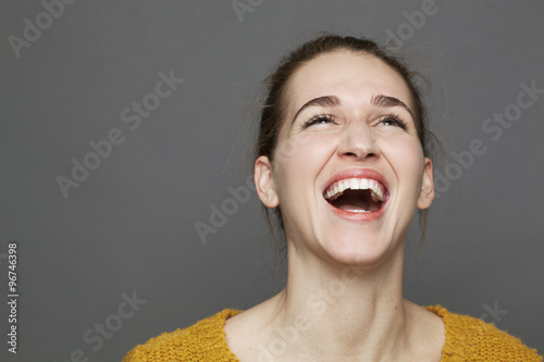 glowing happiness concept - beautiful 20s girl bursting out laughing for wellbei Fototapeta