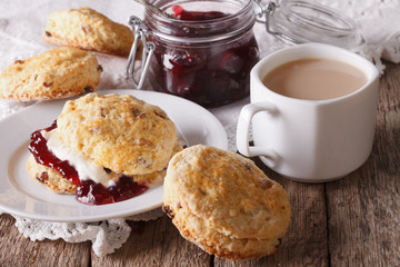 Scones with jam and tea with milk on the table. horizontal