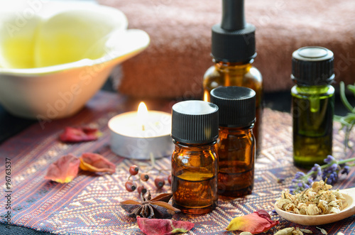 Fotografie, Obraz  essential oils with herbs and candle for aromatherapy treatment
