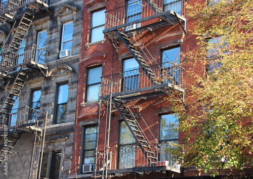Perspective Of Fire Escape Ladders On Apartment Building Block