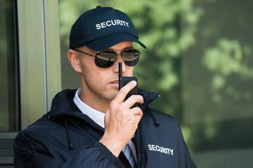 Młody ochroniarz rozmawia walkie-talkie