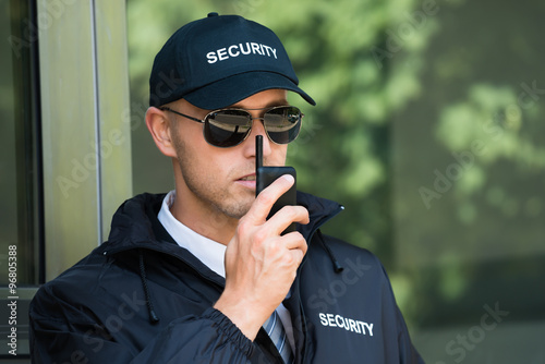 Fotografia  Young Security Guard Talking On Walkie-talkie