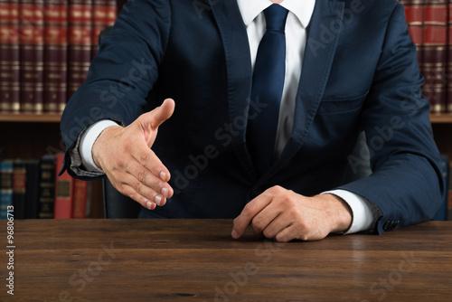 Lawyer Offering Handshake At Desk In Courtroom Wallpaper Mural