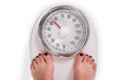 Woman's Legs On Weighing Scale Over White Background