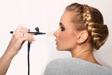 Portrait Of A Beautiful Young Blonde Woman On A Light Background. There Is Hand With Aerograph Making An Airbrush Make Up. Hair Tied In A Braid. Copy Space..