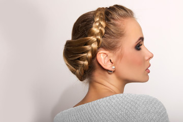 Fototapetaportrait of a beautiful young blonde woman on a light background with hairdo on her head. copy space.
