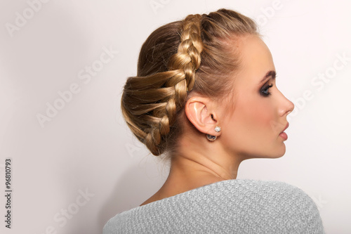 portrait of a beautiful young blonde woman on a light background with hairdo on her head. copy space. - 96810793