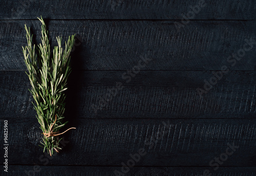 Fotografie, Obraz  A bunch of rosemary on a black wooden background with a free space top view