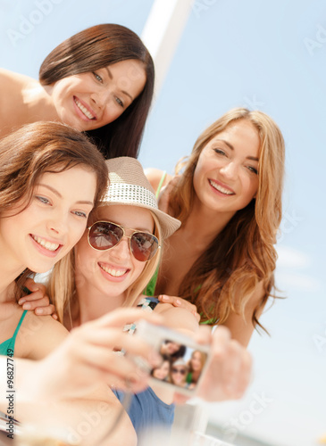 Smiling Girls Taking Photo In Cafe On The Beach Buy This