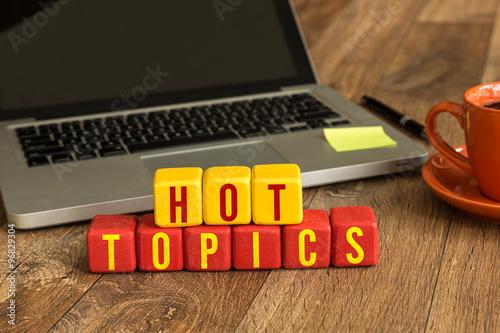 Fotografie, Obraz  Hot Topics written on a wooden cube in a office desk